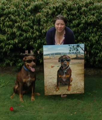 Sarah McBride the artist with one of her paintings and Kevin the Kelpie